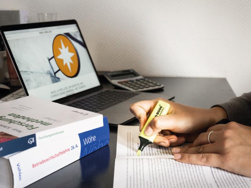 Bücher, Laptop und Blatt mit schreibender Hand