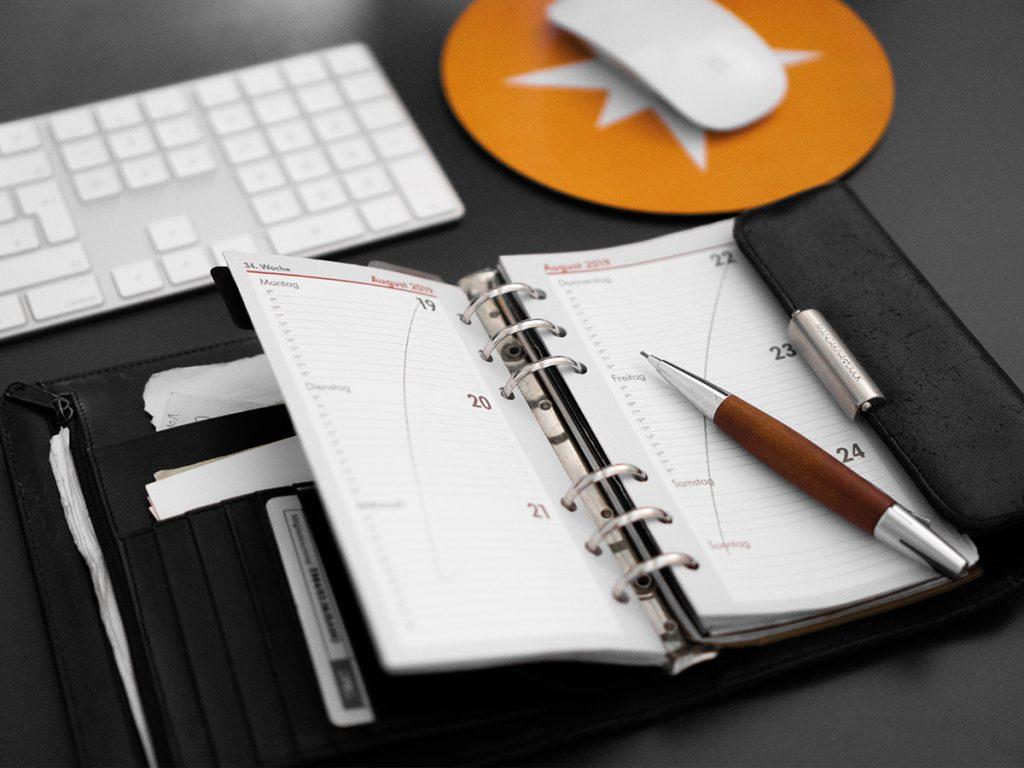 analoger Kalender mit Tastaur und Maus im Hintergrund